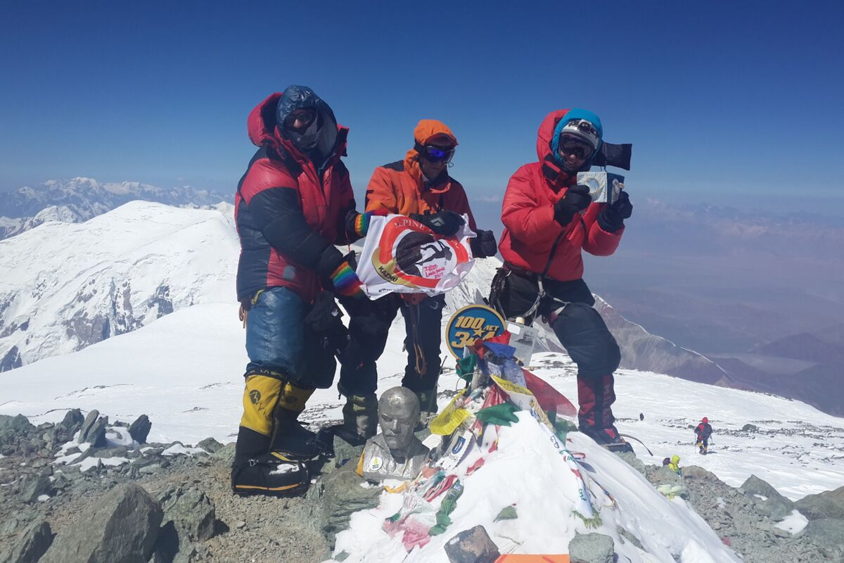 Three climbers on the summit of Pik Lenin