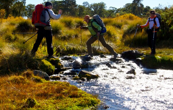 Participant jumping over a river at Mount Kenya (Photo: SummitClimb & Felix Berg)