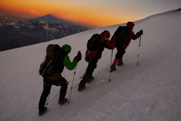 Sunrise on Elbrus, 3 mountaineers climbing to the top of Europe.